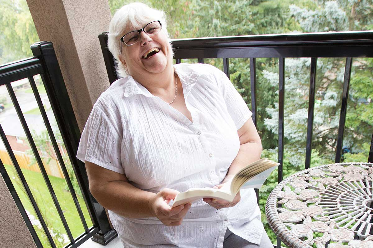 Resident enjoying reading a book outdoors on balcony