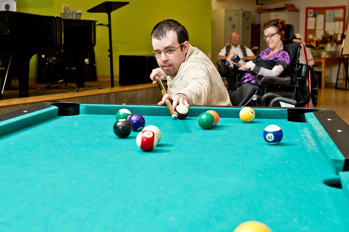 Resident playing billiards in recreation area